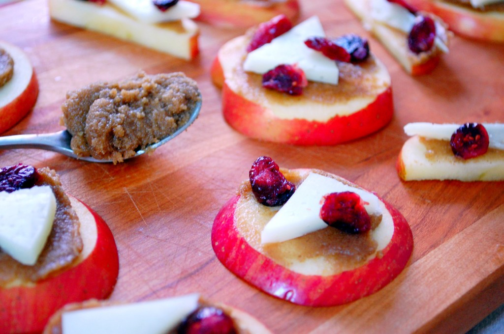 A great gluten-free appetizer of apple slices topped with walnut butter, manchego cheese and cranberries