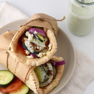 This Greek Veggie Pita Sandwich with Parsley Tzatziki is the perfect way to dress up a veggie burger into a meal. It's perfect for a comforting Greek-themed dinner. | uprootkitchen.com